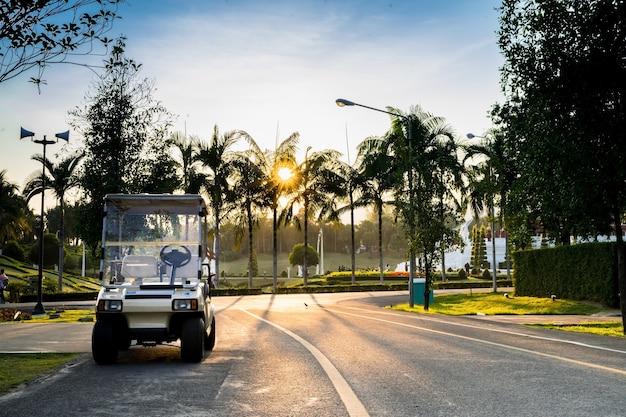 Wózki golfowe lub samochody golfowe w ogrodzie piękne na zachód słońca