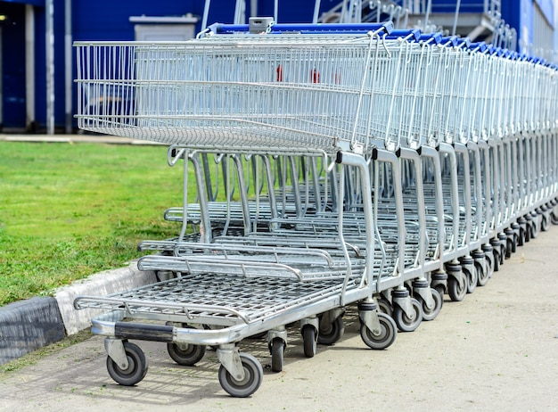 Wózki sklepowe na parkingu dużego centrum handlowego.