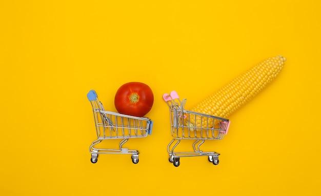 Wózki supermarketów z huśtawką kukurydzy i pomidorów na żółtym tle.