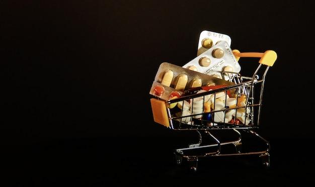 Wózki supermarketowe wypełnione kapsułkami medycznymi na czarnym tle