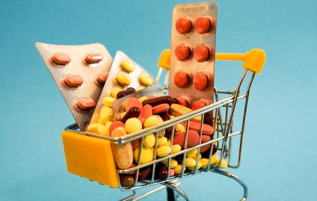 Wózki supermarketowe wypełnione kapsułkami medycznymi na kolorowym tle