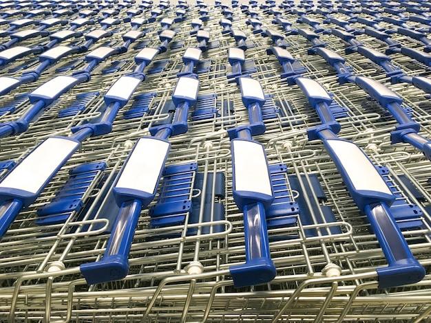 Wózki z niebieskimi uchwytami są zaparkowane przed supermarketem