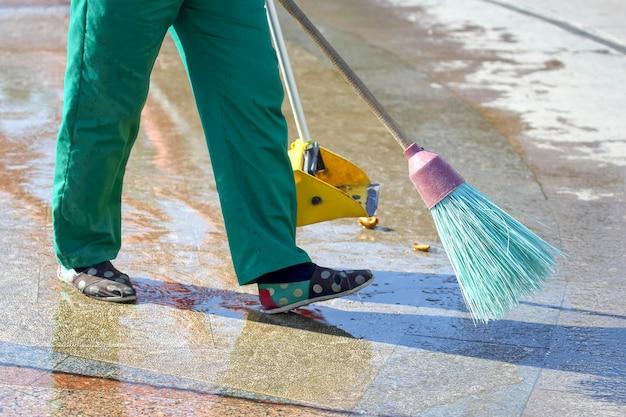 Woźny czyści chodnik miasta z opadłych liści. utrzymanie czystości w mieście