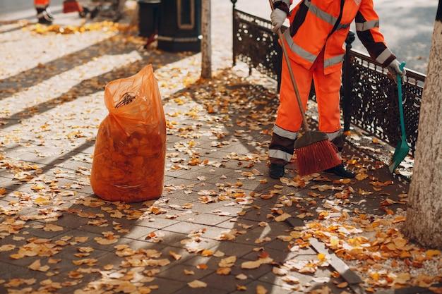 Woźny sprzątaczka zamiata jesienne liście na ulicy
