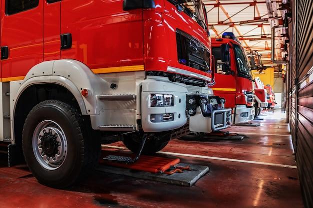 Wozy strażackie zaparkowane w straży pożarnej przygotowane do akcji.