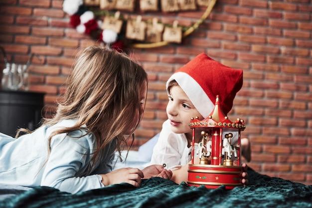 Wpatrują się w siebie. dzieci bawią się zabawkową karuzelą w nowym roku. jedna dziewczyna ma na głowie czapkę mikołaja.