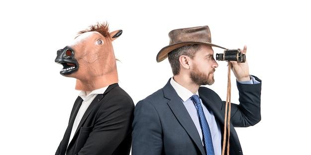 Wpatrując się w dal. profesjonalni mężczyźni noszą głowę konia i kowbojski kapelusz. dziwni biznesmeni. firmowa impreza kostiumowa. firmowe halloween. to po prostu absurd.