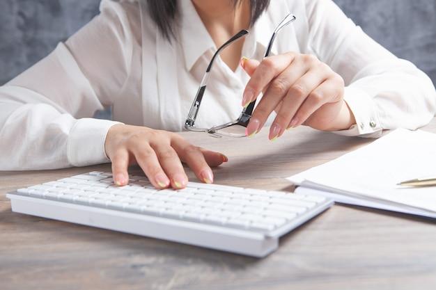Wpisując na klawiaturze kobiece ręce. okulary optyczne