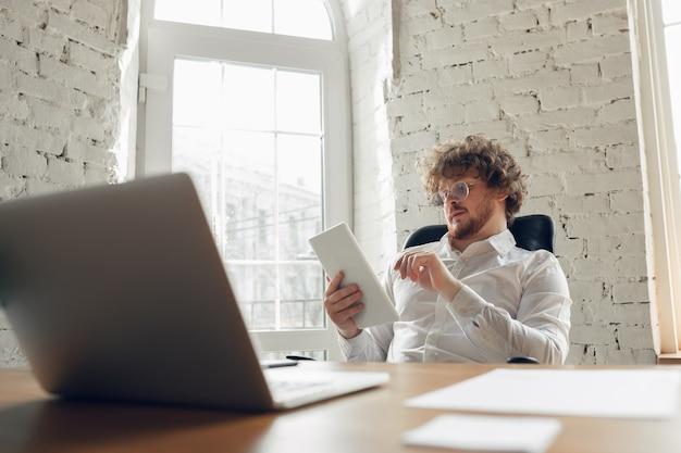 Wpisywanie tekstu, analizowanie, surfowanie. kaukaski młody człowiek w biznesie strój pracy w biurze. młoda kobieta, kierownik wykonujący zadania z smartphone, laptop, tablet ma konferencję online, studia.