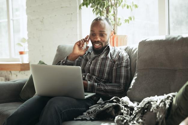 Wpisywanie tekstu i rozmowa przez telefon. mężczyzna, freelancer podczas pracy w domowym biurze podczas kwarantanny. młody biznesmen w domu, samodzielnie na białym tle. korzystanie z gadżetów. praca zdalna, zapobieganie rozprzestrzenianiu się koronawirusa.