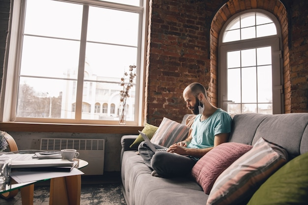 Wpisywanie tekstu. młody mężczyzna robi jogę w domu podczas kwarantanny i pracy online jako freelancer.