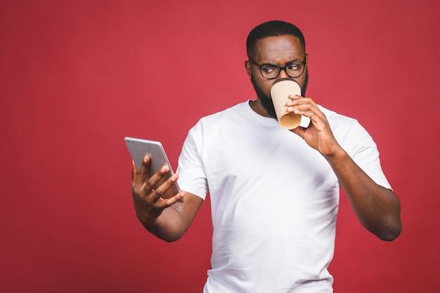 Wpisywanie wiadomości rozochocony murzyn pisać na maszynie coś na telefonie komórkowym, pije kawę podczas gdy stać odizolowywam przeciw czerwonemu tłu.