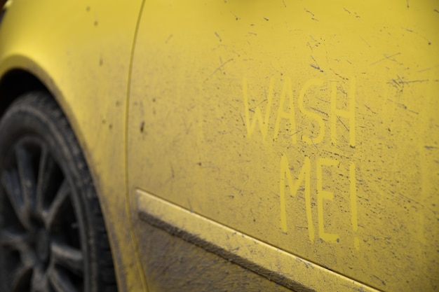 """Wpisz tekst napisu """"umyj mnie"""" na bardzo brudnej powierzchni samochodu. myjnia samochodowa koncepcyjna."""