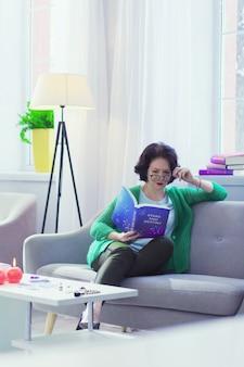 Wpływ gwiazd. poważna inteligentna kobieta czytająca książkę, ciesząc się astrologią