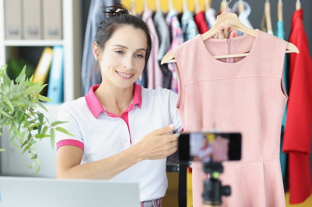 Wpływowa młoda kobieta transmituje na żywo przegląd sukienek w domowej pracy studyjnej vlogera