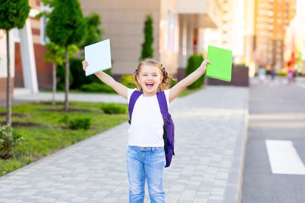 """Wracając do szkoły, szczęśliwa uczennica z plecakiem trzyma w rękach podręczniki, idąc do pierwszej klasy i krzycząc """"hurra"""""""
