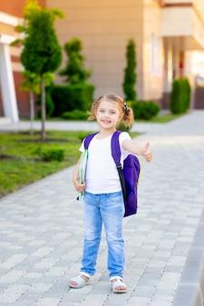 Wracając do szkoły, uczennica z plecakiem i książką w rękach idzie na naukę do pierwszej klasy i radośnie pokazuje klasie kciuk w górę