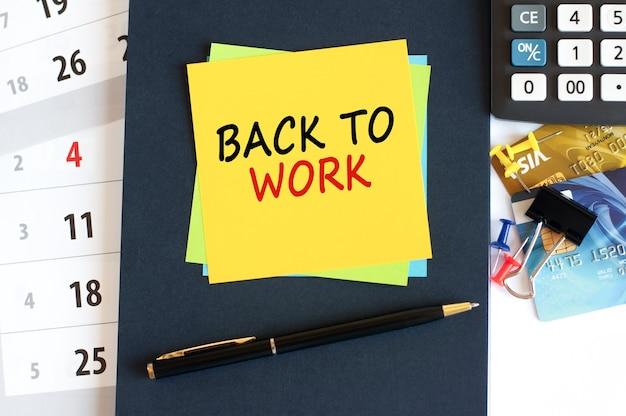 Wracam do pracy, tekst na żółtym papierze w kształcie kwadratu. notatnik, kalkulator, karty kredytowe, długopis, artykuły papiernicze na pulpicie. koncepcja biznesowa, finansowa i edukacyjna. selektywna ostrość.