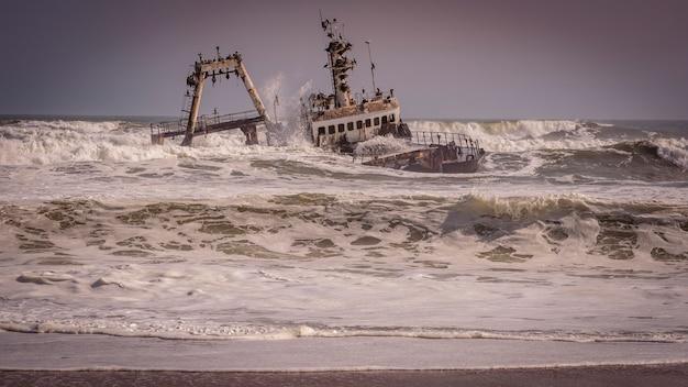 Wrak splatał na plaży w oceanie atlantyckim w szkieletu wybrzeża parku narodowym w namibia, afryka.