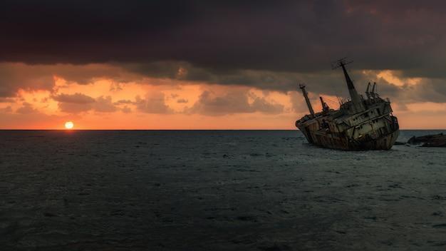 Wrak statku (edro iii) o zachodzie słońca w pobliżu paphos, cypr. długi czas ekspozycji