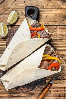 Wrap fajitas tortilla z paskami mięsa wołowego, kolorową papryką i cebulą oraz salsą.