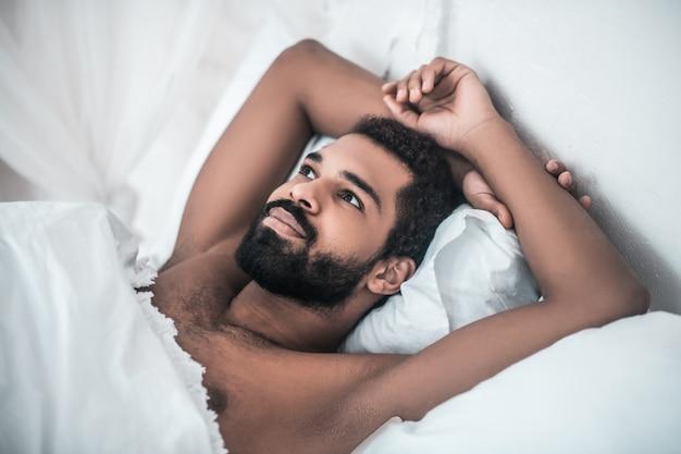 Wrażenie snu. atrakcyjne zraszanie afroamerykanin patrząc zamyślony leżąc w łóżku rano w dobrym nastroju
