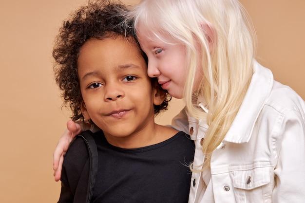 Wrażliwa albinos dziecko dziewczynka przytula afrykańskiego chłopca na białym tle