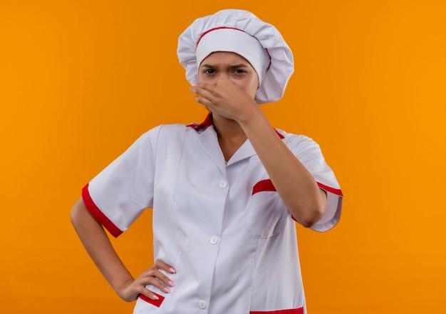 Wrażliwa młoda kobieta kucharz na sobie mundur szefa kuchni zamknięty nos kładąc rękę na biodrze na na białym tle pomarańczowy
