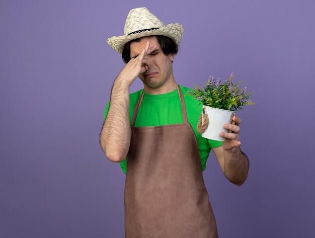 Wrażliwy młody męski ogrodnik w mundurze na sobie kapelusz ogrodniczy trzyma kwiat w doniczce i trzyma nos