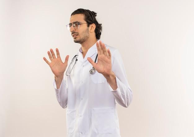 Wrażliwy młody mężczyzna lekarz z okularami optycznymi na sobie białą szatę ze stetoskopem podnosząc ręce na odosobnionej białej ścianie z miejsca na kopię