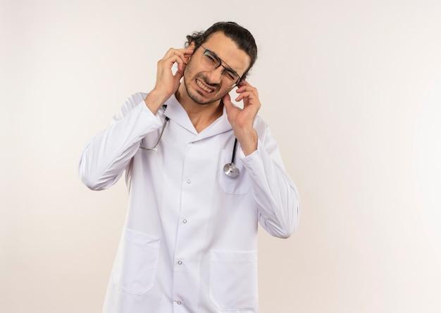Wrażliwy młody mężczyzna lekarz z okularami optycznymi na sobie białą szatę ze stetoskopem zamknięte uszy na izolowanej białej ścianie z miejsca na kopię