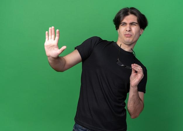 Wrażliwy młody przystojny facet na sobie czarną koszulkę trzymając okulary pokazując gest stopu na białym tle na zielonej ścianie