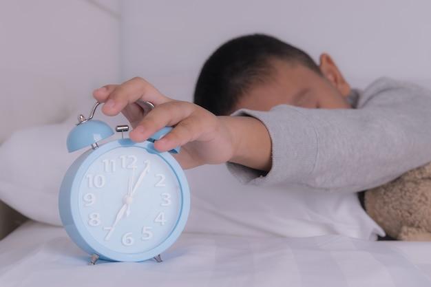 Wręcza chłopiec dosięga out dla budzika na ranku. zarządzanie czasem