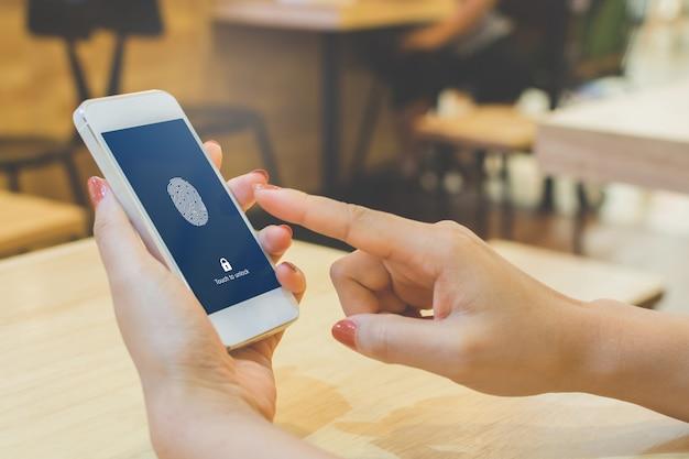 Wręcza kobiety trzyma smartphone i skanuje odcisk palca biometryczną tożsamość dla odblokowywa jej telefon komórkowego