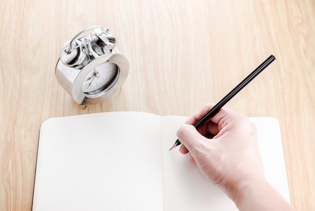 Wręcza trzymać czarnego ołówek i pisać na pustym miejscu otwiera notatnika z budzikiem obok go na drewnianym stole