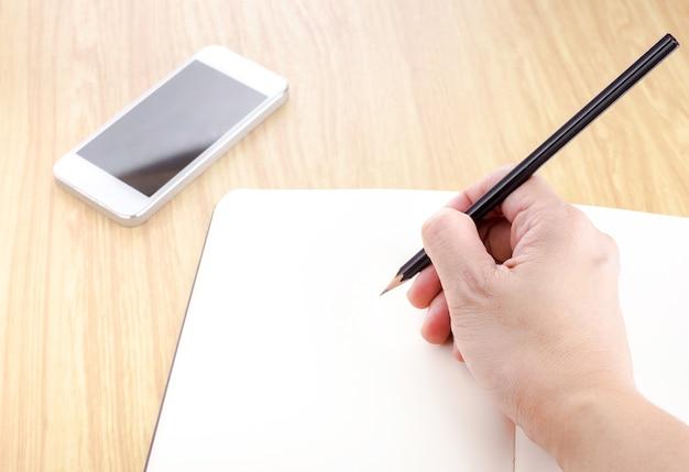 Wręcza trzymać czarnego ołówek i pisać na pustym miejscu otwiera notatnika z smartphone obok go na drewnianym stole