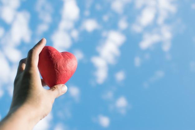 Wręcza trzymać czerwonego dekoracyjnego serce przeciw niebieskiemu niebu.