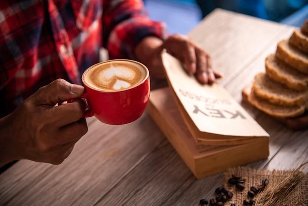 Wręcza trzymać filiżankę kawy i czytać książkowego klucz sukces - pojęcie styl życia