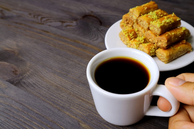 Wręcza trzymać filiżankę turecka kawa z talerzem baklava ciasta na stole