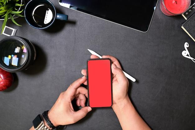 Wręcza trzymać nowożytnego mądrze telefon z odosobnionym pustym ekranem dla mockup na biurowym biurku