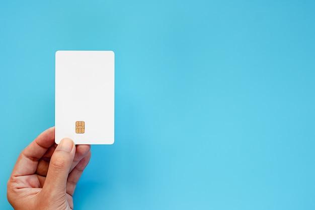 Wręcza trzymać pustą kredytową układ scalony kartę na błękitnym tle
