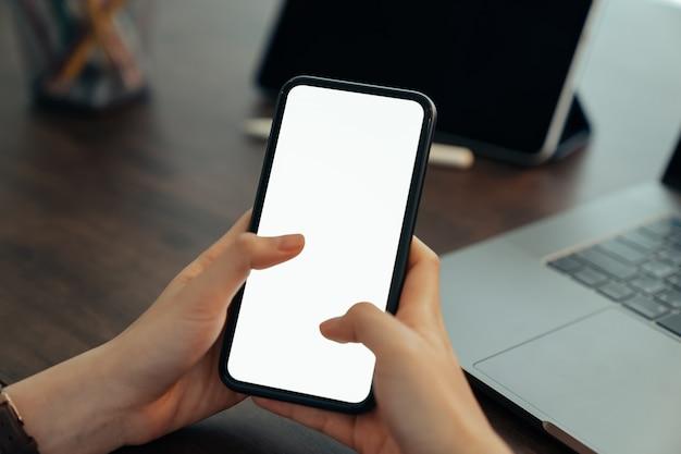 Wręcza trzymać pustego ekran smartphone na biurka biurze i dla graficznego pokazu montażu.