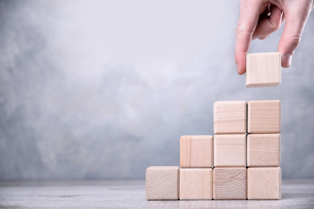 Wręcza układać drewnianego bloku sztaplowanie jako kroka schodek na drewnianym stole. koncepcja biznesowa dla sukcesu procesu wzrostu. skopiuj miejsce