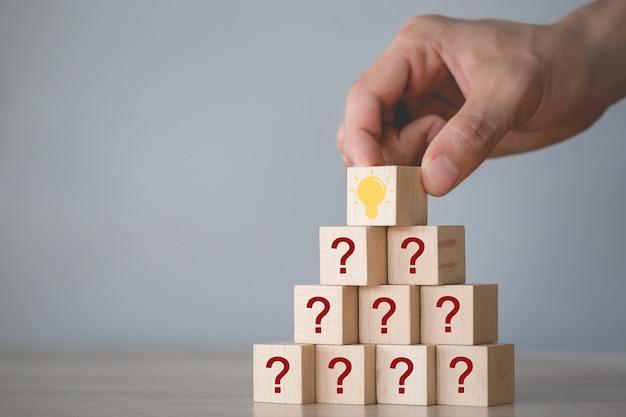 Wręcza układać drewnianego bloku sztaplowanie z ikona znakiem zapytania i lampą myśleć z znaka zapytania pojęciem ,.