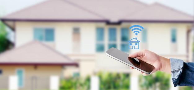 Wręcza używać mądrze telefon z mądrze domową kontrola ikoną nad plamy domu tłem, mądrze kontrola domu pojęcie