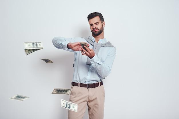 Wreszcie bogaty, nowocześnie wyglądający brodaty mężczyzna rozrzuca dolary, stojąc na szarym tle