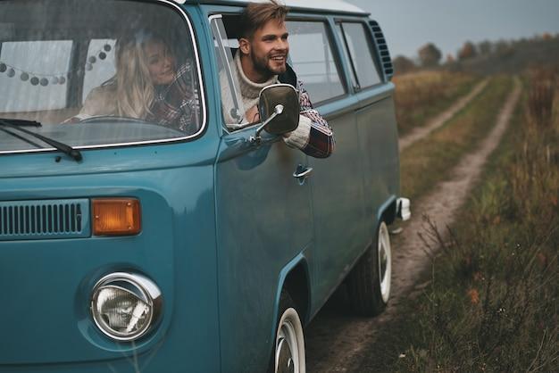 Wreszcie cieszę się podróżą. przystojny młody mężczyzna wychyla się przez okno furgonetki i uśmiecha się siedząc na przednim fotelu pasażera razem z dziewczyną