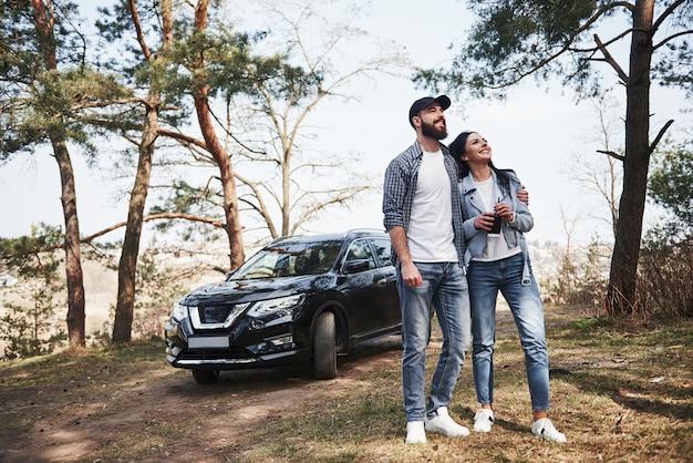 Wreszcie słoneczny dzień. ogarnięcie i cieszenie się naturą. para przyjechała do lasu swoim nowym czarnym samochodem