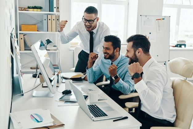 Wreszcie sukces. grupa młodych, nowoczesnych mężczyzn w strojach formalnych, uśmiechających się i gestykulujących podczas pracy w biurze