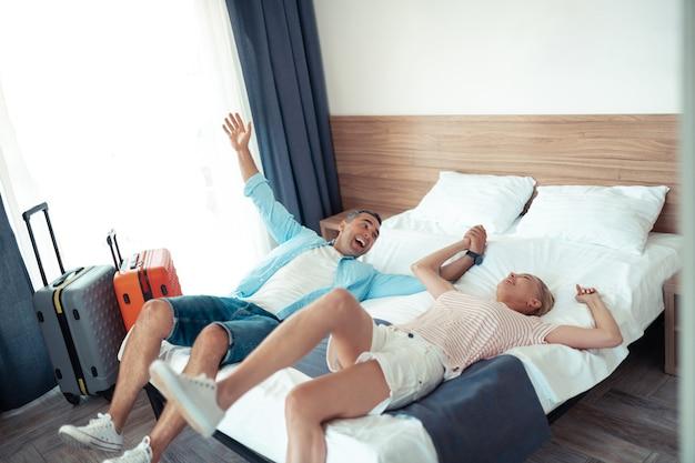 Wreszcie za darmo. wesoły i szczęśliwy mąż i żona leżąc na łóżku hotelowym i trzymający się za ręce świętują swoje wymarzone wakacje.